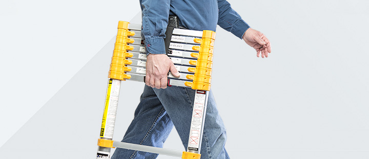 man carrying xtend + climb lightweight telescoping ladder with one hand